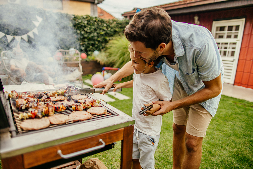 Dad barbecuing with son